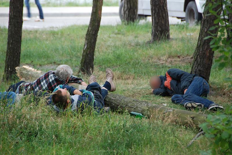 Girti žmonës (vyrai) miega (guli) ant žolës. Benamiai Bomžai Girtavimas Alkoholizmas Buitis