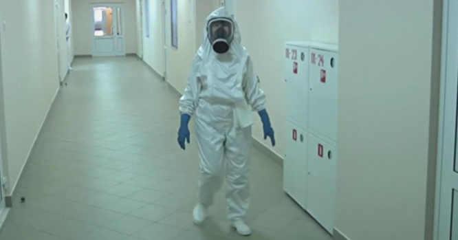 Gydytojas su antivirusiniu kombinezonu