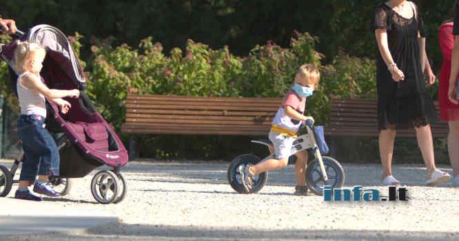 Vaikas su dviračiu ir kauke