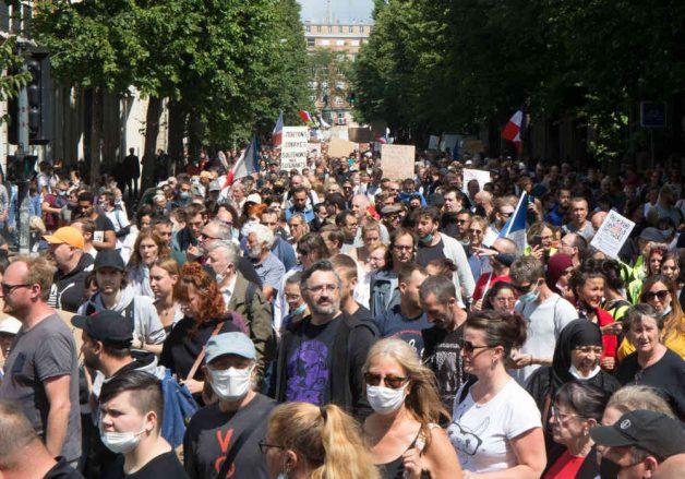 2021 m. Liepos 31 d. Protestuotojai laiko plakatus demonstracijoje prieš sveikatos pasą Lilyje, Prancūzijoje.