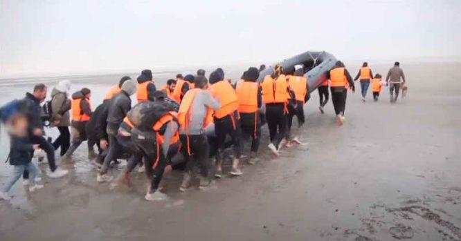 Nelegalūs migrantai neša valtį, ruošdamiesi keliauti į Britaniją